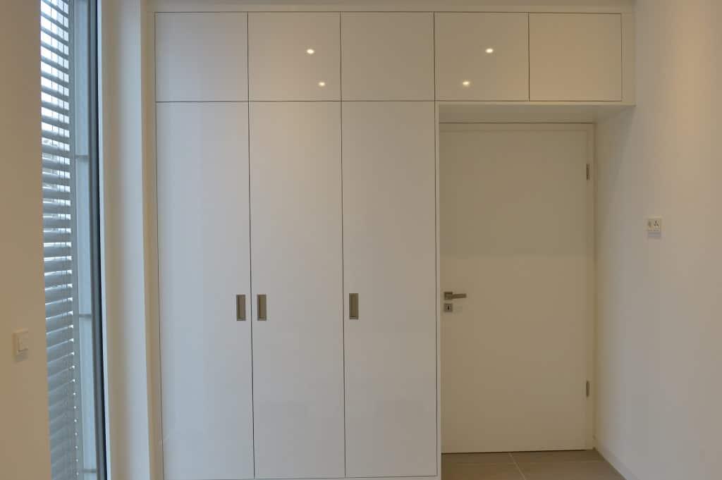 Schrankwand nach Maß in Weiß um eine Tür